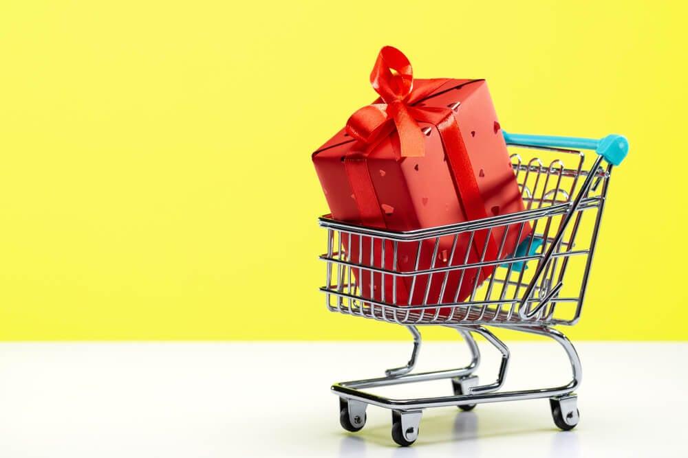 ilustraçao demonstrando carrinho de compras com embrulho vermelho em seu interior em fundo amarelo