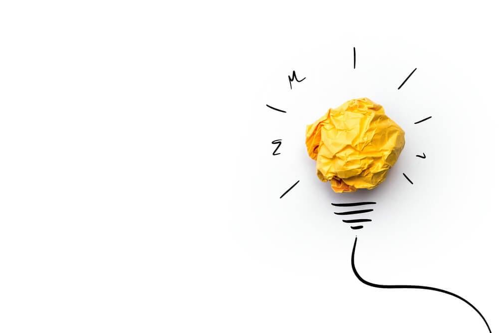 ilustraçao significando a criatividade com papel amassado e traços em sua volta fazendo parecer uma lampada acesa