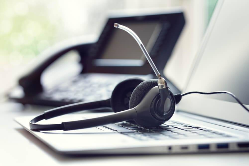laptop , telefone e microfone utilizados por profiddionais em vendas por telefone