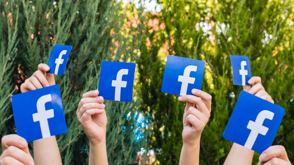 logos da rede social facebook sendo levantadas por mãos