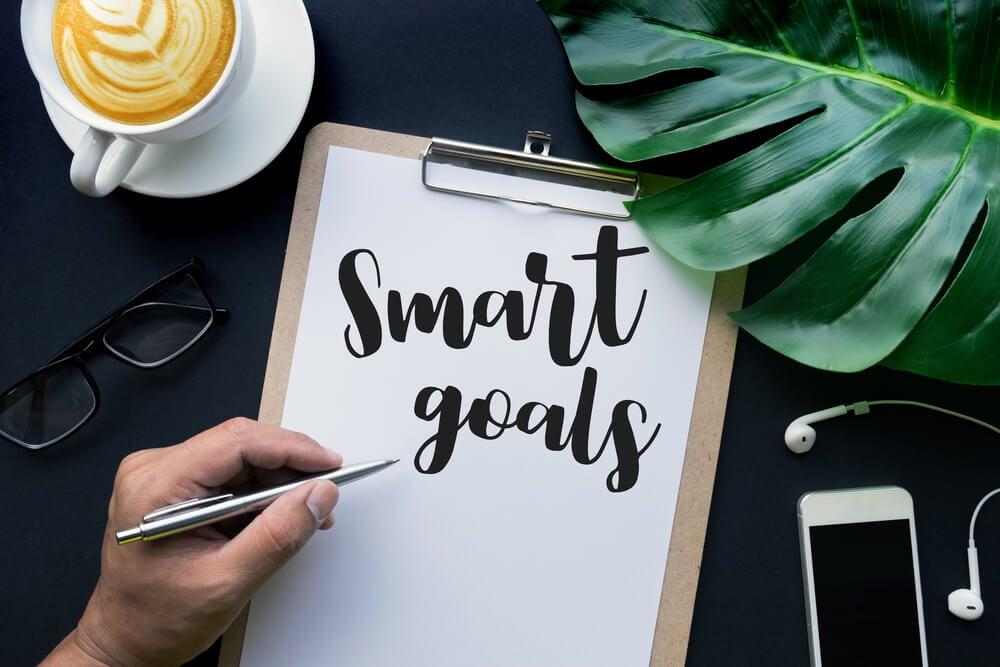 mão feminina escrevendo smart goals em prancheta