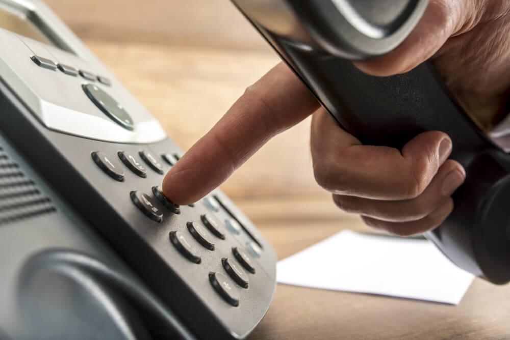 mao masculina apertando botao de telefone ao iniciar venda por telefone