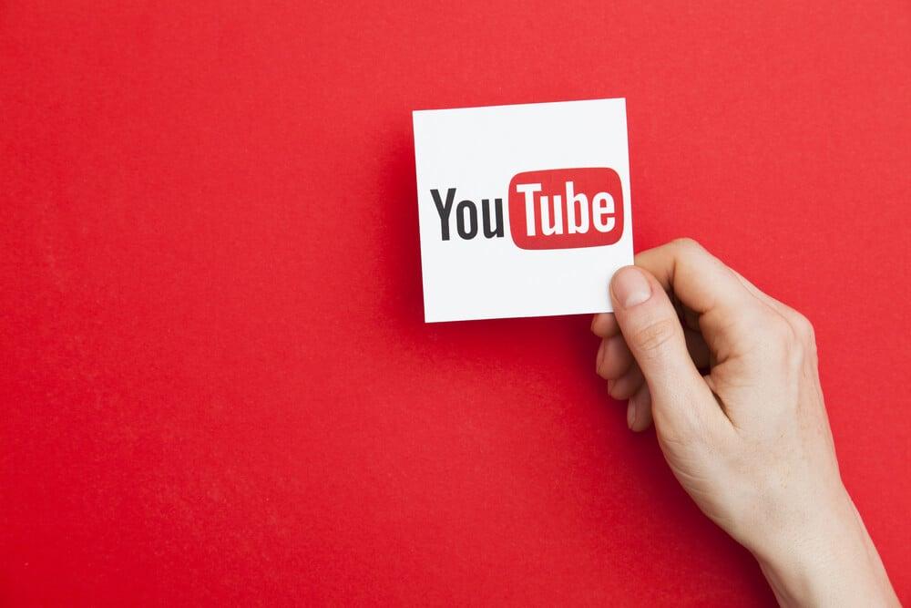 mao masculina segurando papel com icone do aplicativo youtube em fundo vermelho