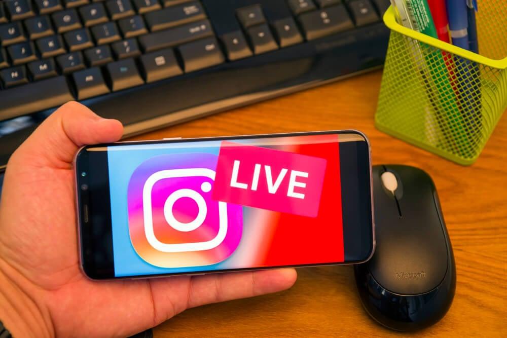 mao masculina segurando smartphone com logo do aplicativo instagram e palavra live em tela em frente a teclado de computador