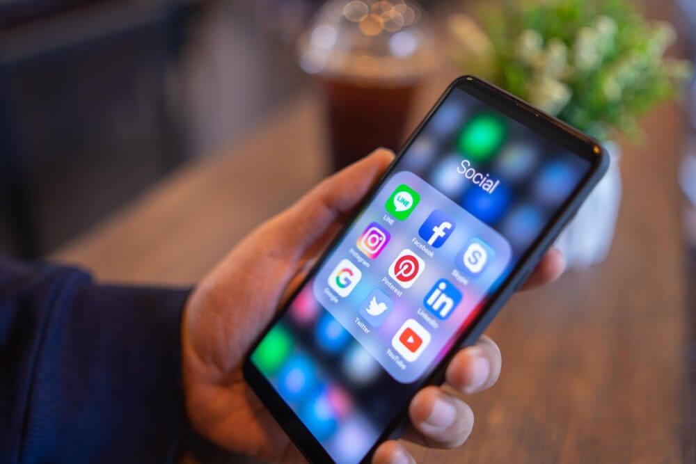 mao masculina segurando smartphone com pasta de aplicativos de redes sociais em tela