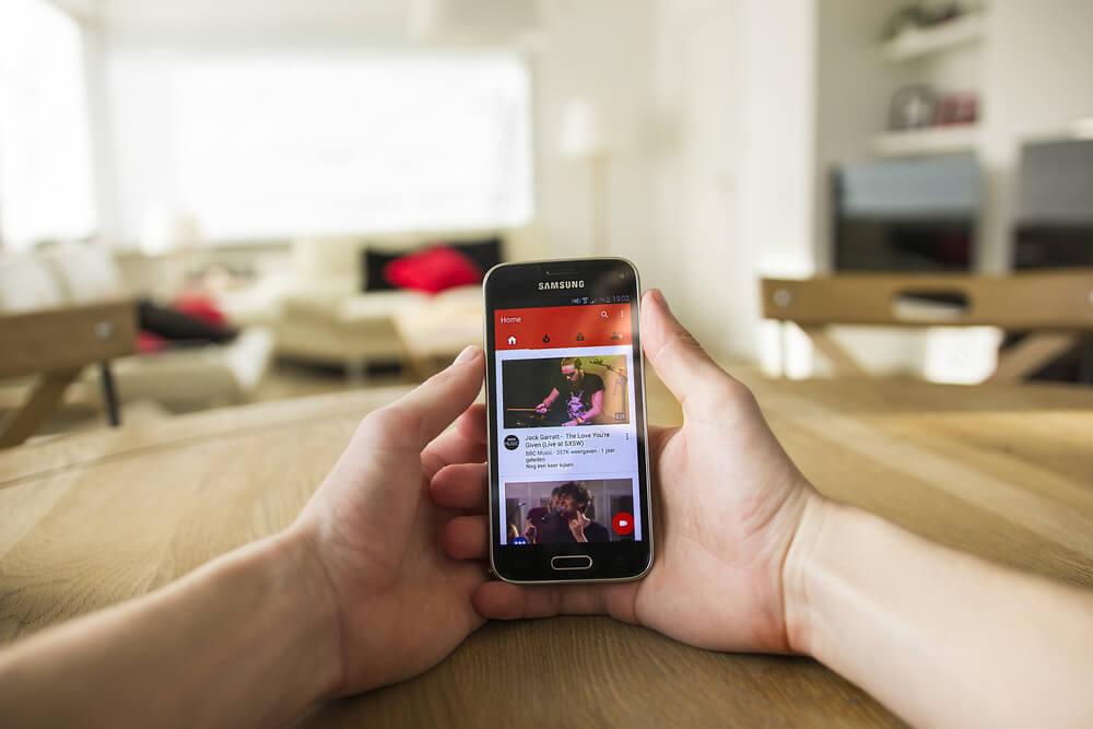 mao masculina segurando smartphone  em pagina inicial do aplicativo youtube e thumbnails de videos em tela
