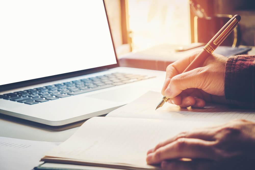 maos masculinas escrevendo redaçao publicitaria em bloco de notas em frente a laptop