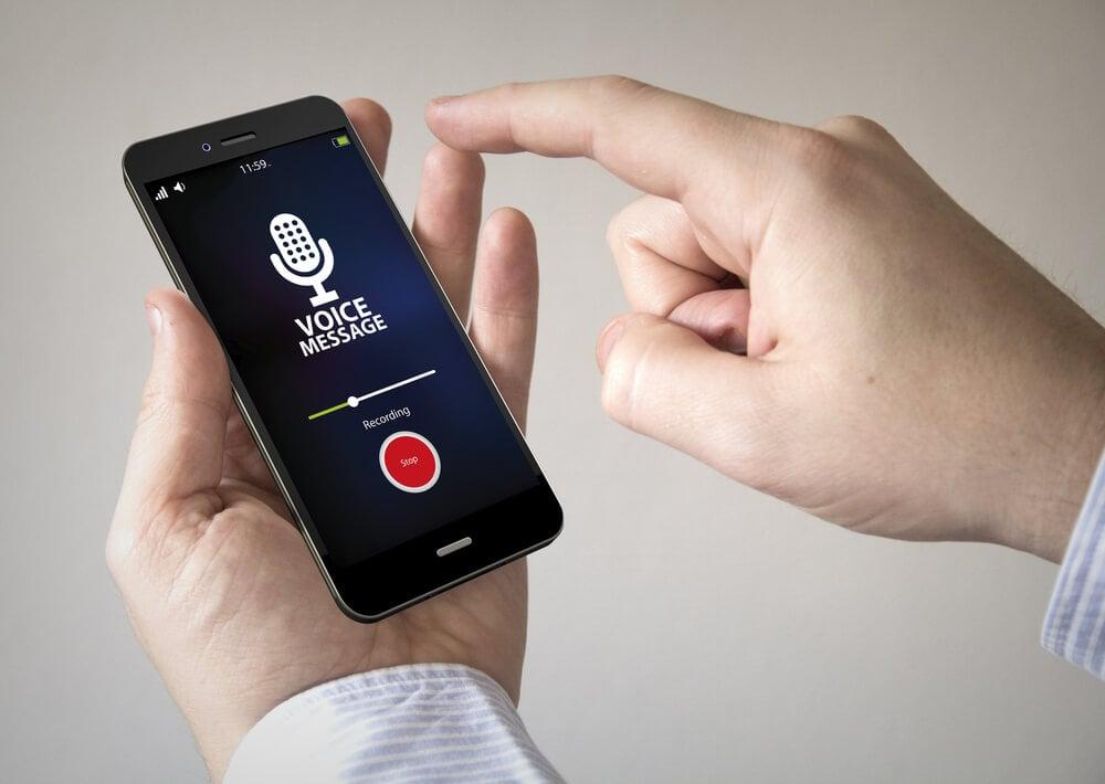 maos masculinas segurando smartphone com gravaçao de voz em tela