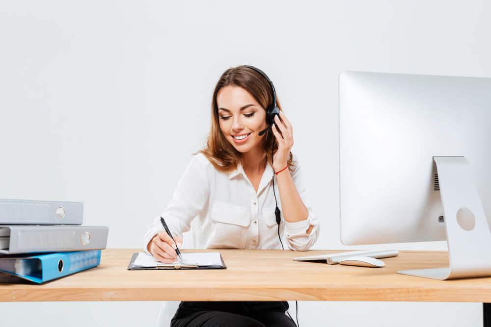 mulher efetuando vendas por telefone enquanto escreve em bloco de anotaçoes em frente a computador em mesa de escritorio