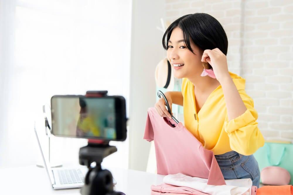 mulher em meio a live do aplicativo instagram sorrindo ao mostrar produtos e roupas