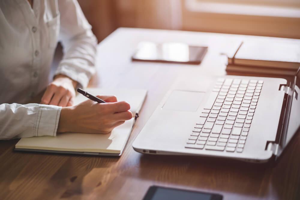 mulher escrevendo em bloco de notas em frente a laptop em mesa de escritorio