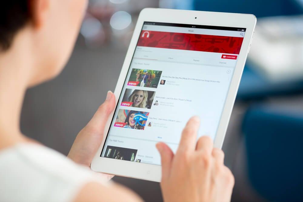 mulher segurando tablet em canal do aplicativo youtube com diversos videos e suas thumbnails em tela
