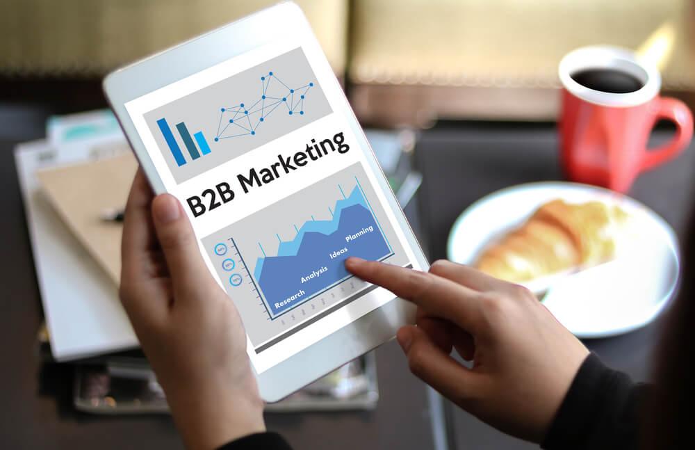 profissional assinalando tablet com tema de B2B Marketing