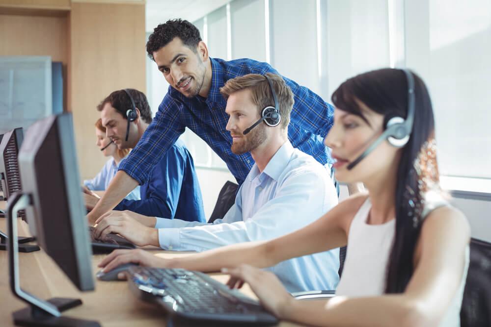 profissional em vendas por telefone em meio a area de trabalho treinando equipe