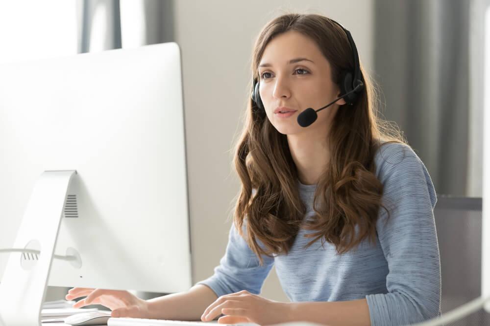 profissional em vendas por telefone exercendo sua profissao concentrada em tela de computador com postura ereta