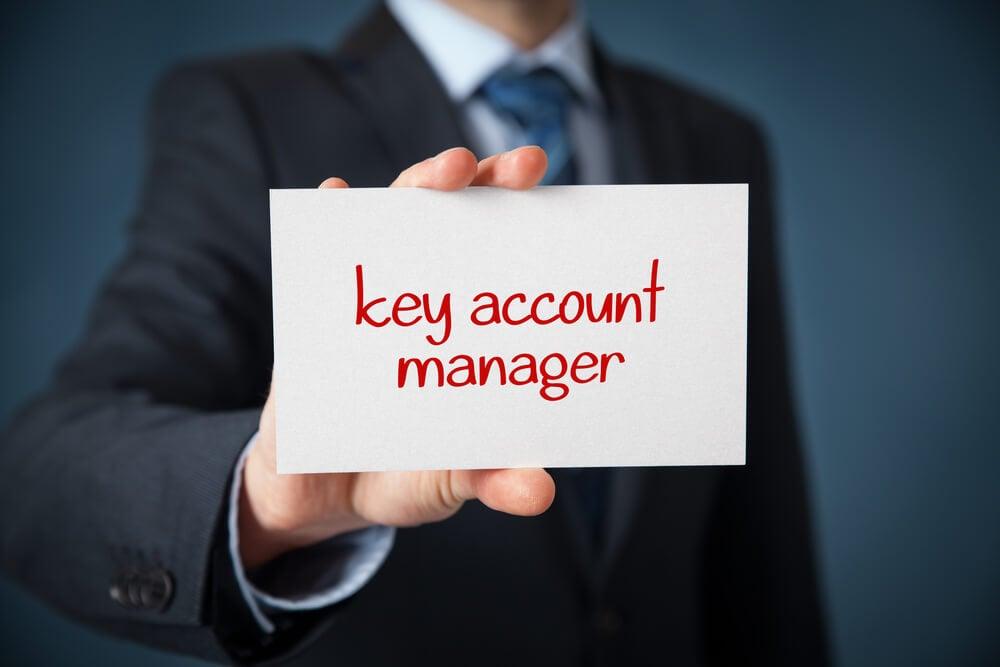 profissional segurando placa entitulada key account manager