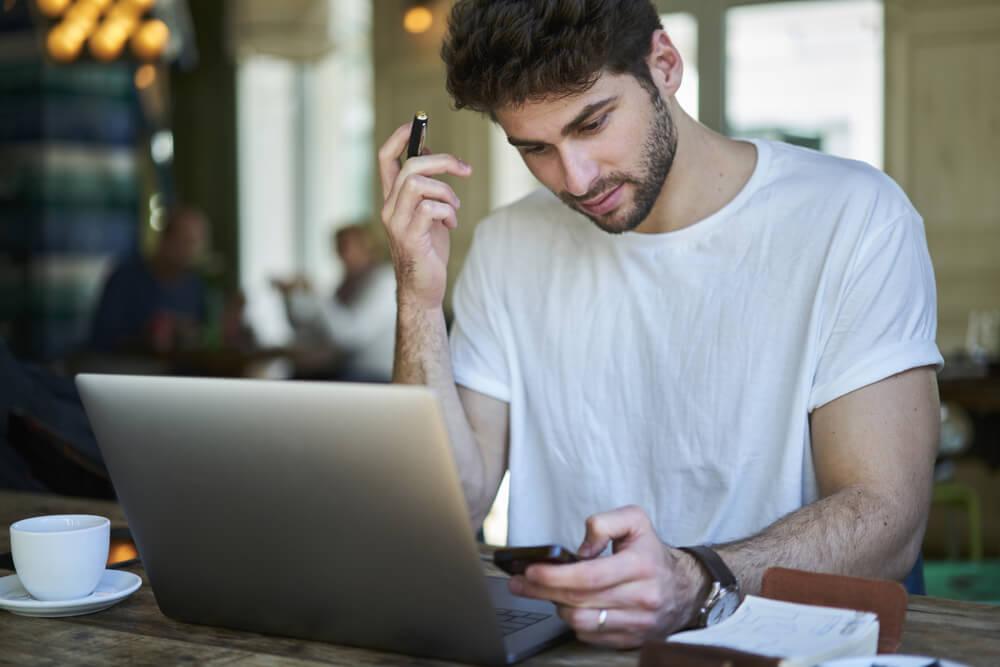 redator pensativo em frente a laptop segurando smartphone com xicara de cafe ao lado ao preparar redaçao publicitaria