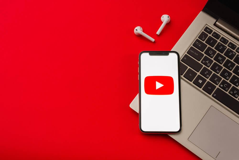 smartphone com icone do aplicativo youtube em tela sob laptop com fones de ouvido ao lado