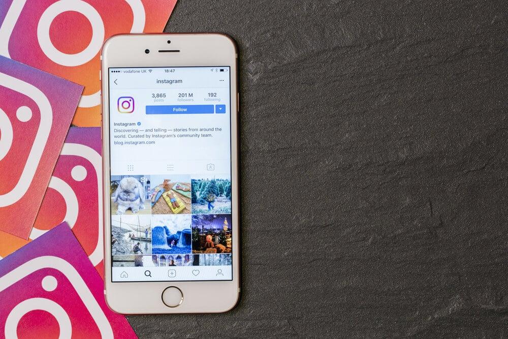 smartphone em cima de mesa com perfil do aplicativo instagram em tela e icones do aplicativo ao lado