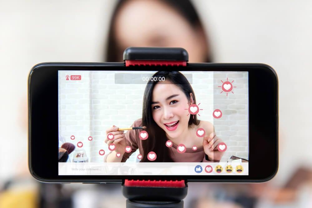 smartphone gravando mulher em meio a live de rede social mostrando produtos de beleza