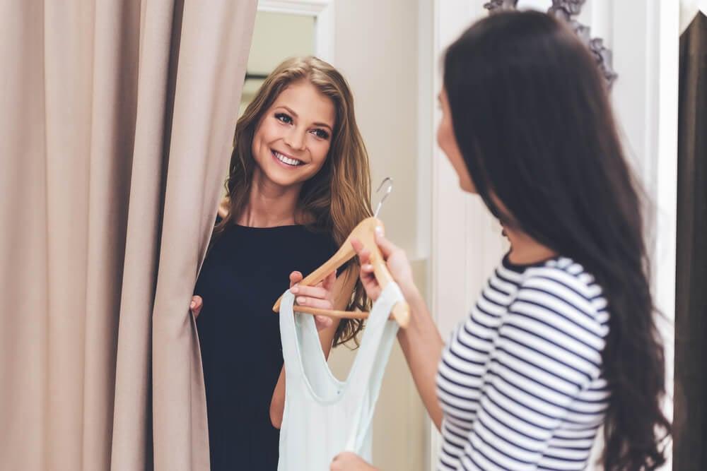 atendente de loja de roupas efetuando atendimento ao entregar roupa para cliente