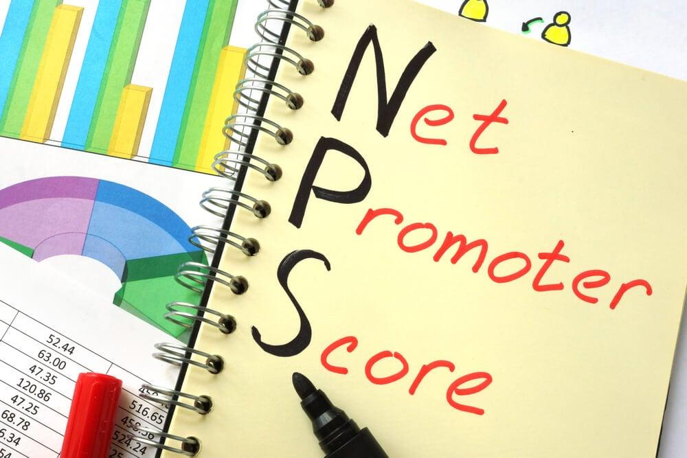 caderno de notas com as palavras net promoter score escritas ao lado de papeis com graficos