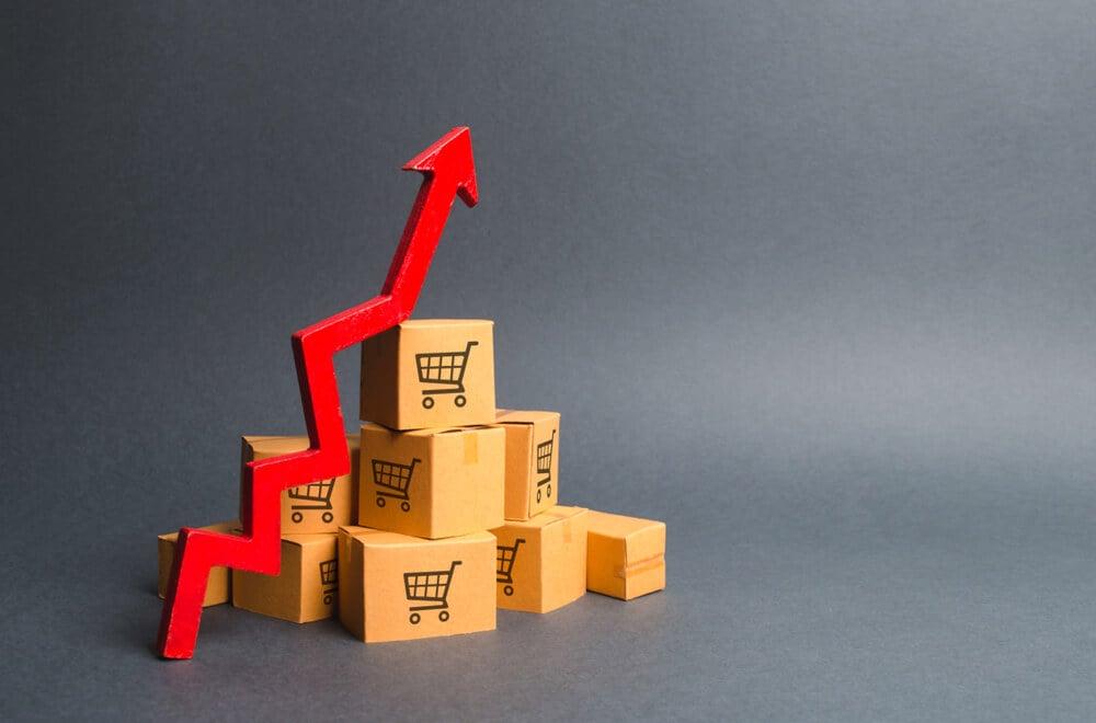 caixas de compras empilhadas com flecha apontando boas vendas