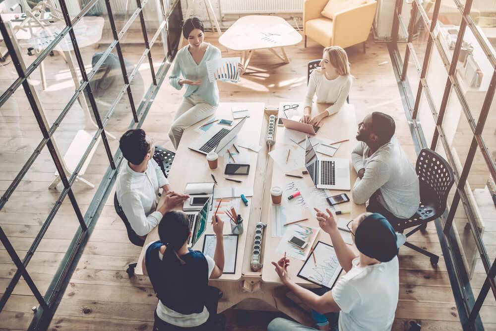 companheiros de trabalho reunidos em mesa executiva com materiais de escritorio espalhados discutindo negocios