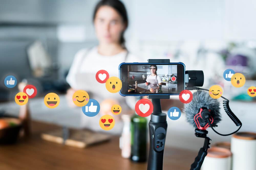 digital influencer criando conteudo de vlog com o tema de culinaria em smartphone com simbolos de reaçoes do aplicativo facebook em sua volta
