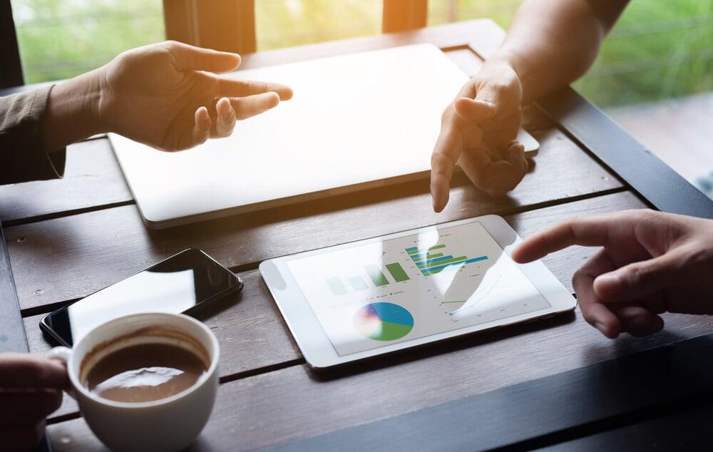 dupla em análise de plano de vendas em mesa de café