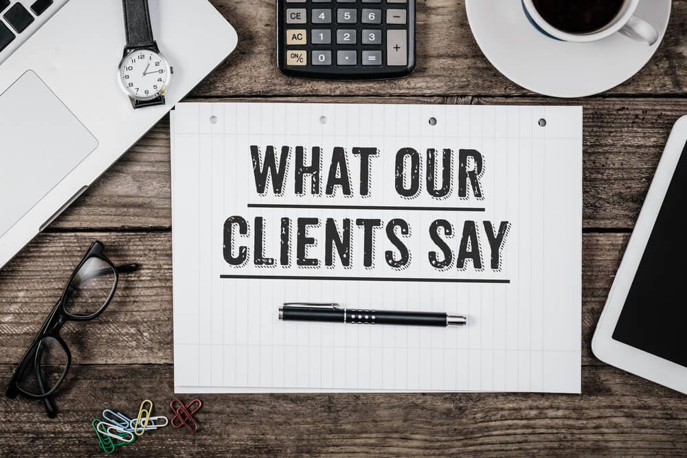 folha de papel sob mesa com a frase what your clients say acima de caneta com materiais de escritorio em sua volta