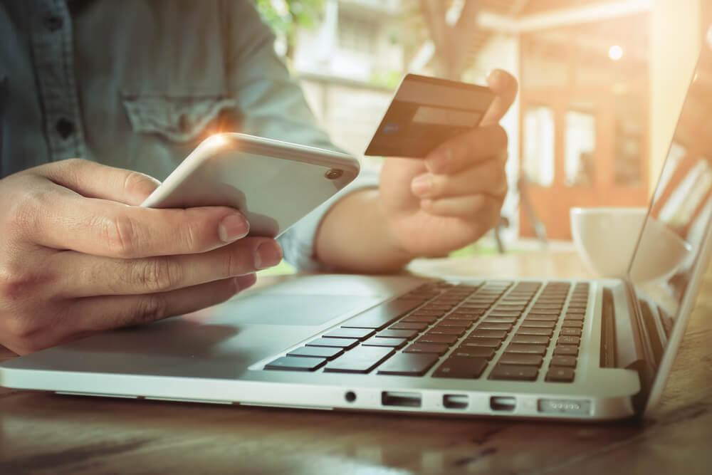 homem em frente a laptop com smartphone e cartao de credito em maos fazendo compras em e-commerce