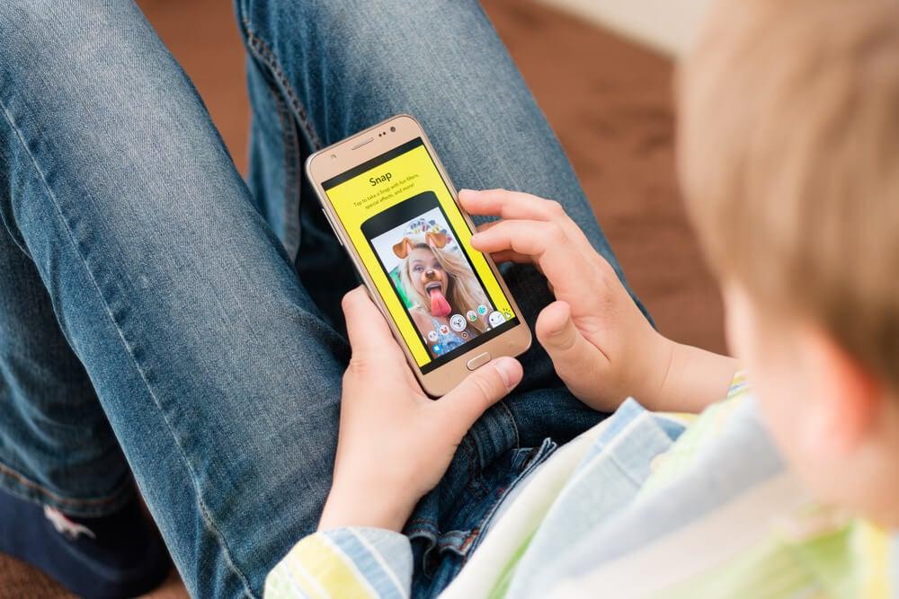 homem sentado com smartphone em maos com aplicativo snapchat em tela