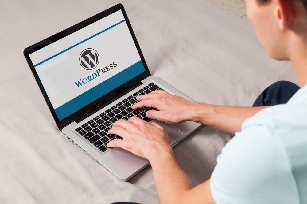 homem teclando em laptop com logo da plataforma wordpress em tela