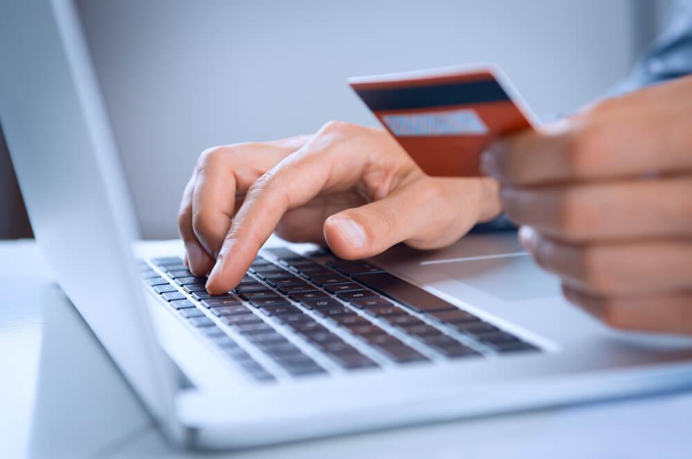 homem usando laptop e segurando cartao de credito simbolizando compras em e-commerce