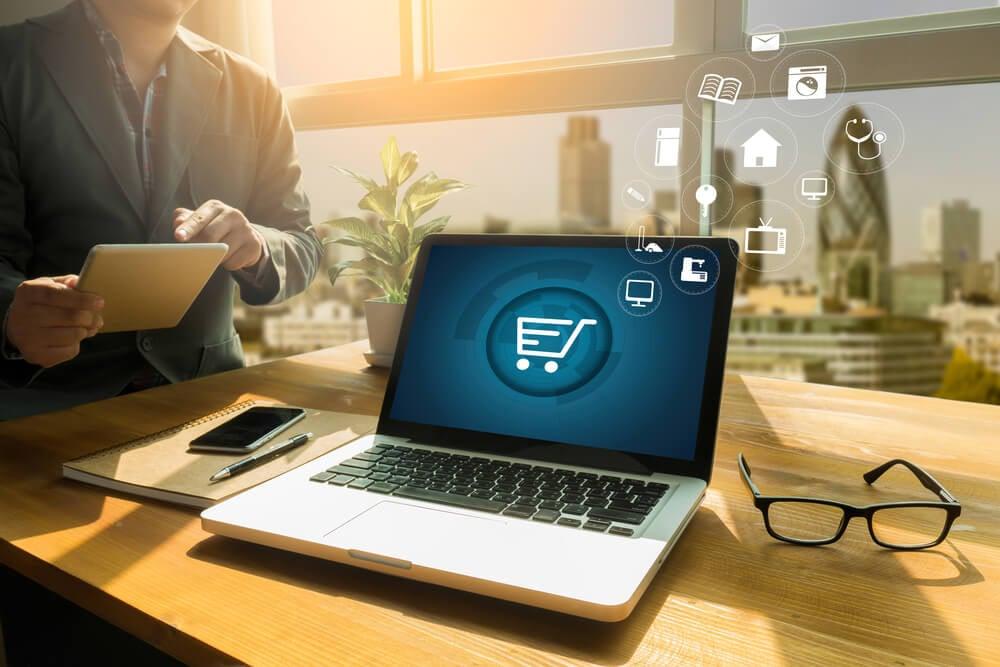 laptop em mesa de escritorio com simbolo de carrinho de compras em tela simbolizando o e- commerce