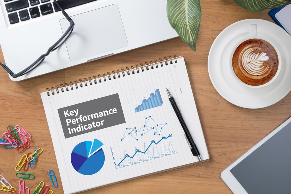 laptop, oculos, bloco de notas e materiais de escritorio sob mesa com graficos e as palavras key performance indicator escritas em caderno