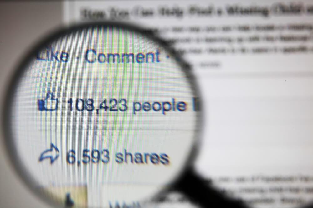 lupa ampliando numero de curtidas e compartilhamentos da plataforma facebook em tela de computador
