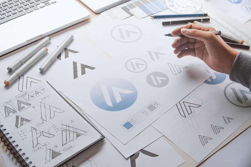 mao masculina escolhendo simbolo para logo de marca em frente a teclado de laptop