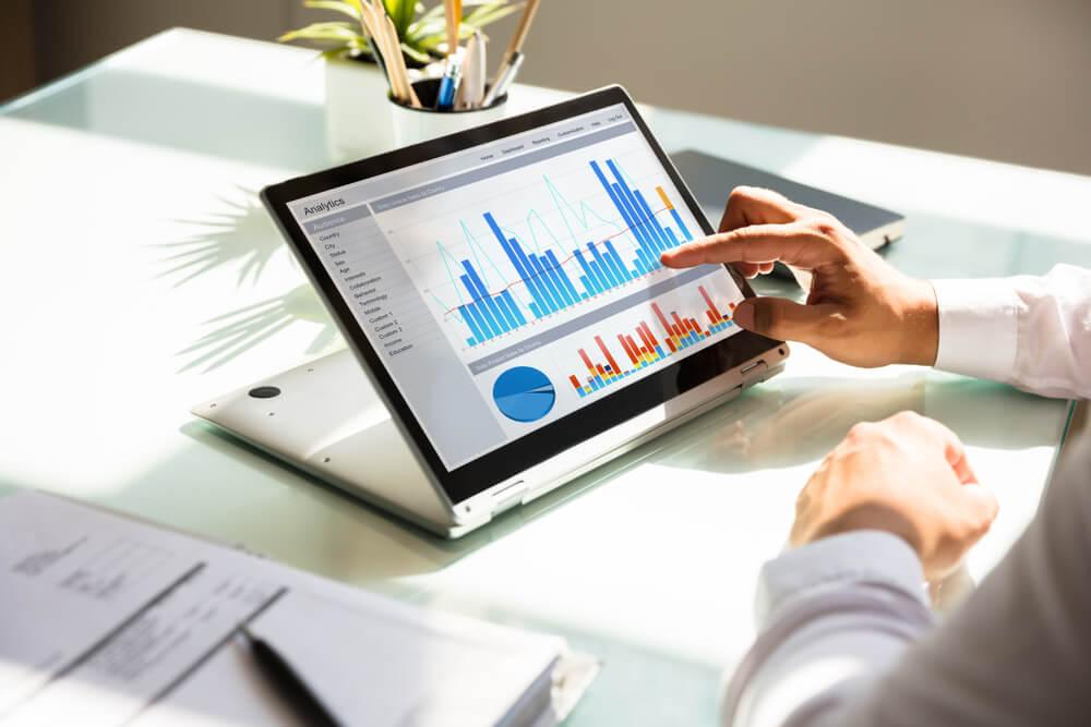 mao masculina indicando graficos em tablet sob mesa de escritorio