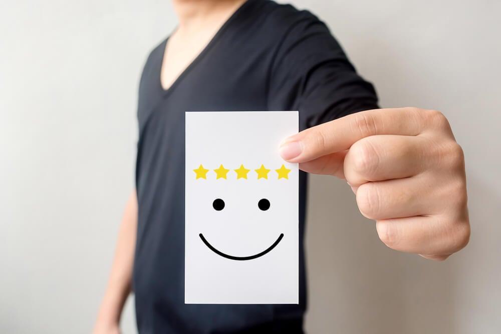 mao segurando nota com rosto feliz significando bom atendimento ao cliente