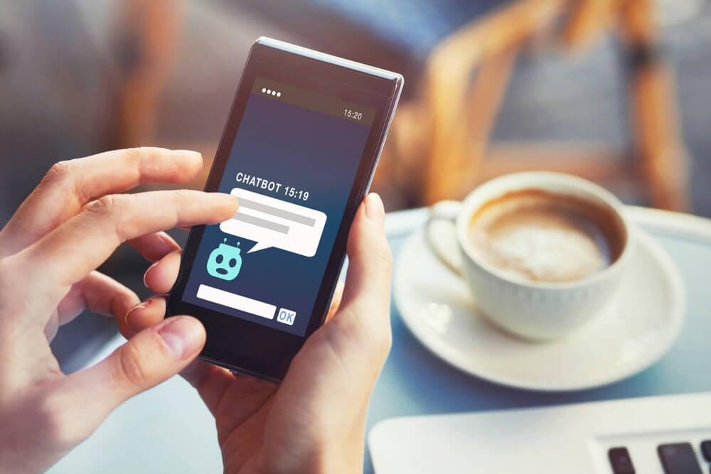 maos femininas segurando smartphone ao conversar com chatbot em cafeteria