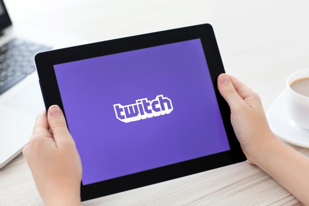 maos femininas segurando tablet com icone de aplicativo twitch em tela