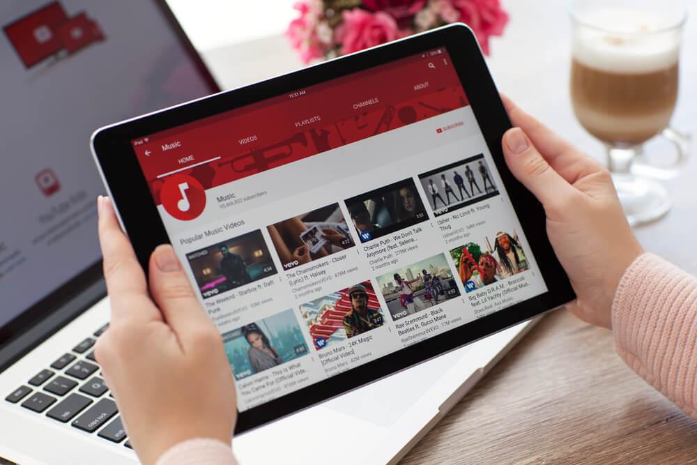 maos femininas segurando tablet em frente a laptop com plataforma youtube em tela com diferentes videos