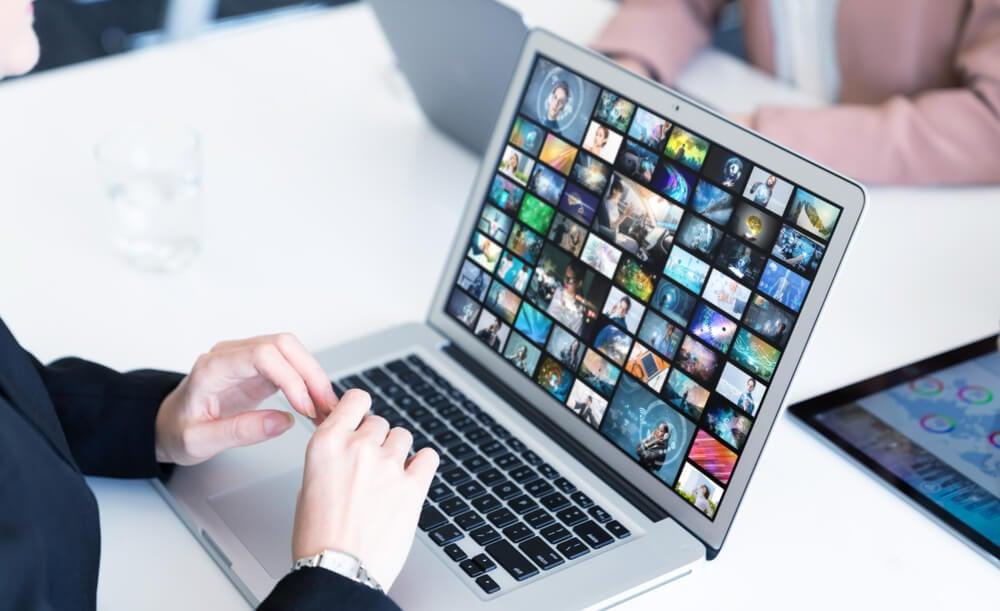 maos masculinas em frente a laptop em mesa de escritorio com diferentes thumbnails em tela