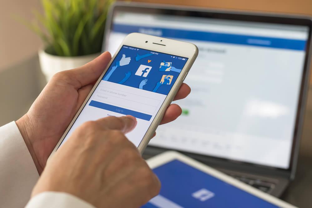 maos segurando smartphone com aplicativo facebook em tela em frente a laptop