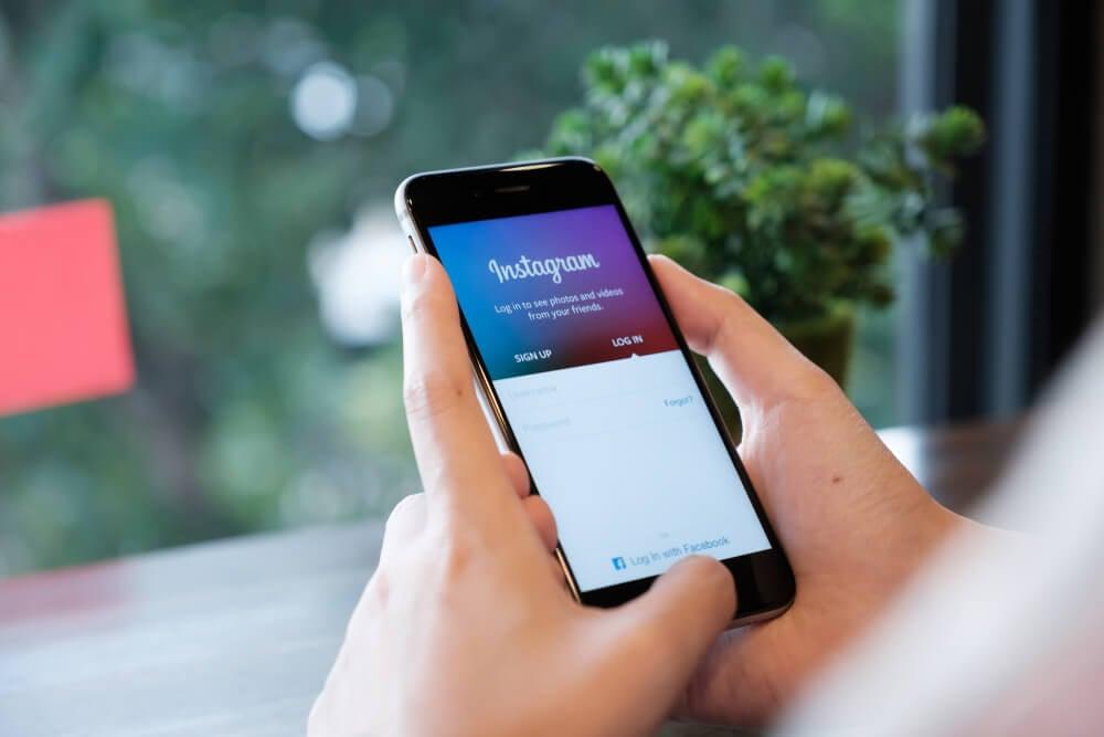 maos segurando smartphone com pagina de login do aplicativo instagram em tela
