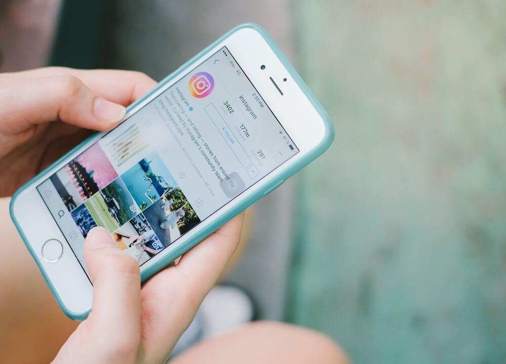 maos segurando smartphone com perfil do aplicativo instagram em tela