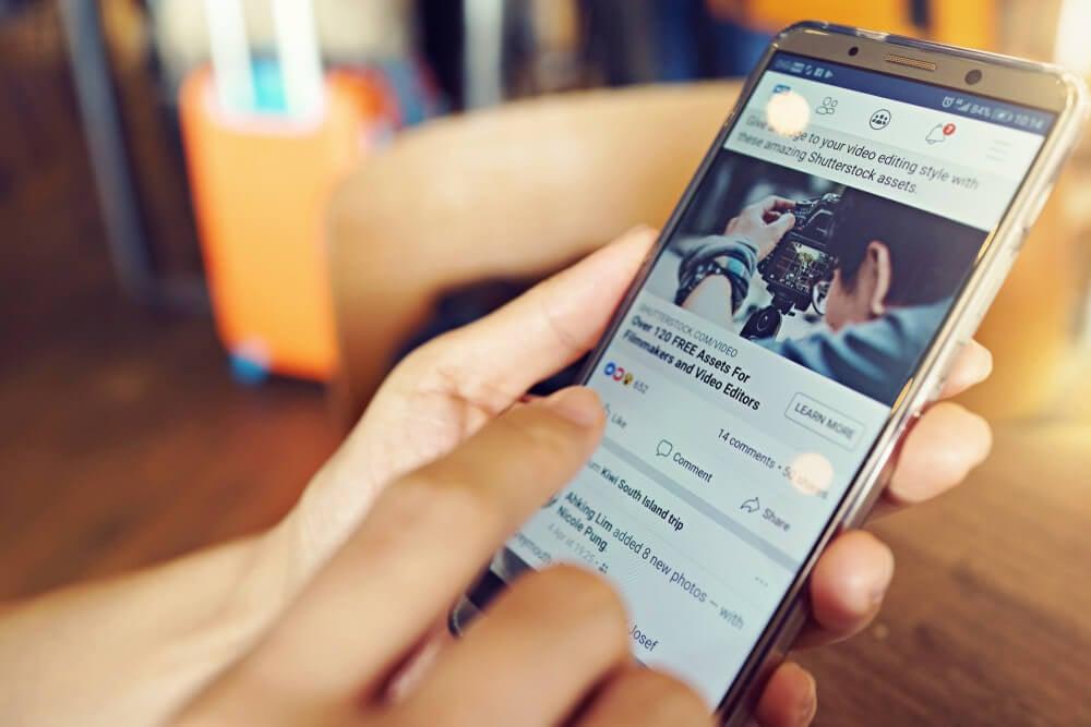 maos segurando smartphone com publicaçao do aplicativo facebook em tela