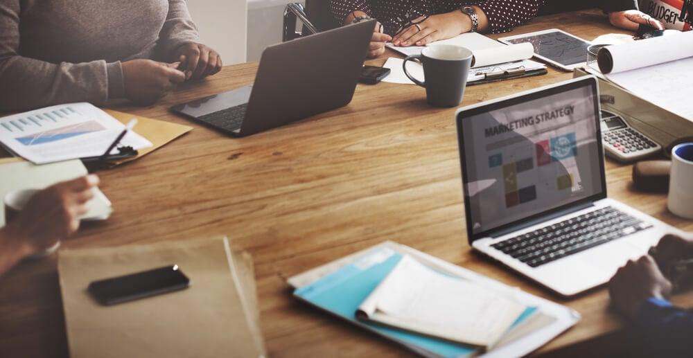 mesa de escritorio com profissionais trabalhando em laptop e materiais de escritorio em sua volta